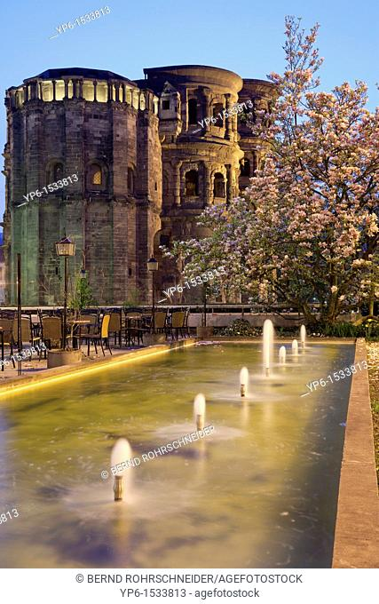 Porta Nigra, World Heritage Site, with fountain and blooming magnolia at night, Trier, Germany