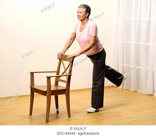 older woman doing gymnastics with a chair - sprawel leg to the back - muscularity - senior
