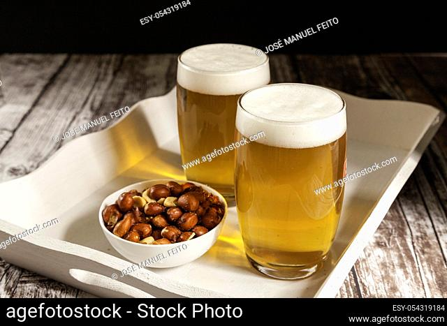 two glasses of beer with a bowl of peanuts in a tray on wooden table