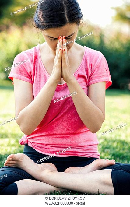 Young woman doing yoga, meditation outside, eyes closed