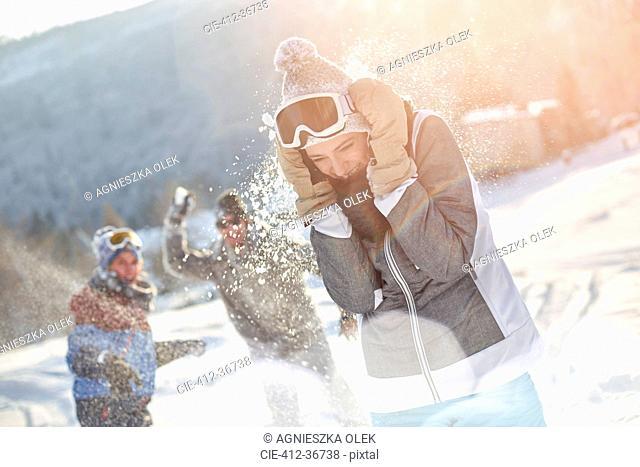 Playful skier friends enjoying snowball fight in snowy field