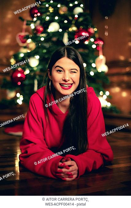 Portrait of winking teenage girl lying on the floor in front of Christmas tree
