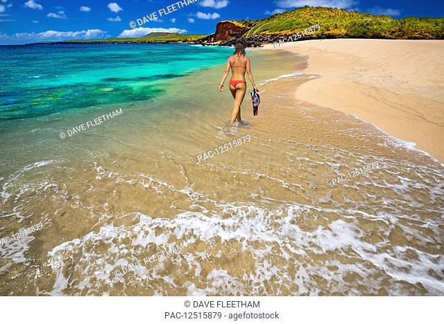 A young woman in a bikini with snorkelling equipment, Kawakiu Nui Beach on Molokai's West end; Molokai, Hawaii, United States of America