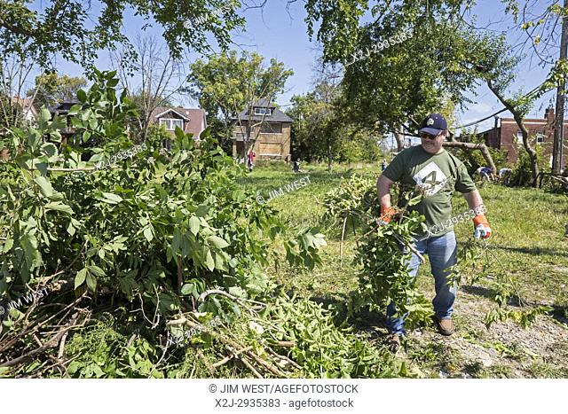 Detroit, Michigan - Community residents and members of the Knights of Columbus clean trash and brush from vacant lots in the Morningside neighborhood