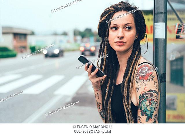 Woman using mobile phone on roadside