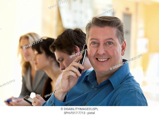 Man talking on a mobile phone and smiling with another passengers on an airport