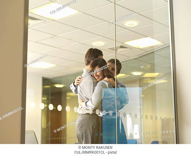 Office staff group hug