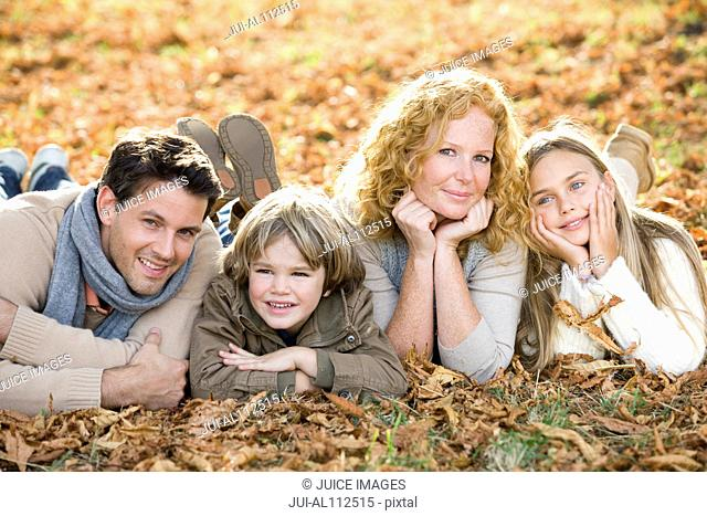 Portrait of family lying on ground in autumn forest