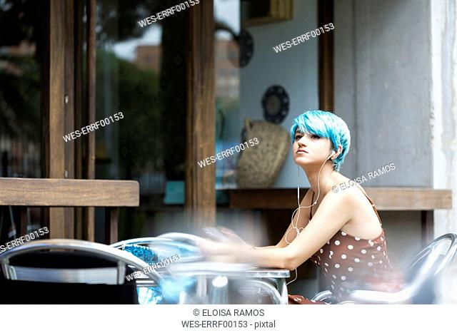 Portrait of young woman with blue dyed hair sitting in a pavement cafe listening music with earphones