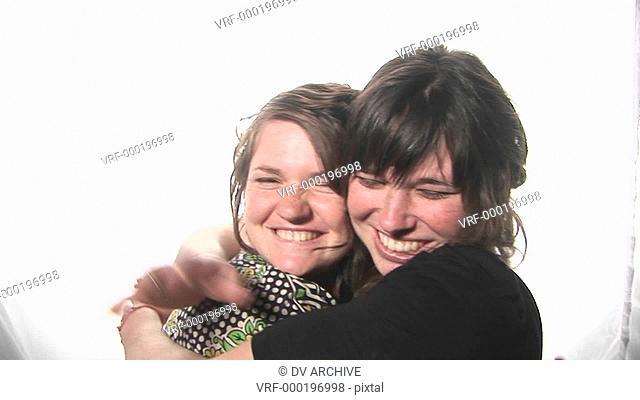 young women happily hug and kiss