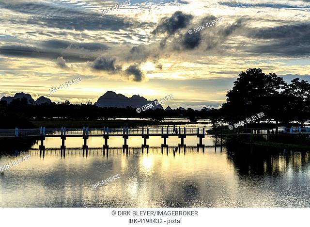 Bridge across artificial lake, sunset above tower karst mountains, Hpa-an, Karen or Kayin State, Myanmar