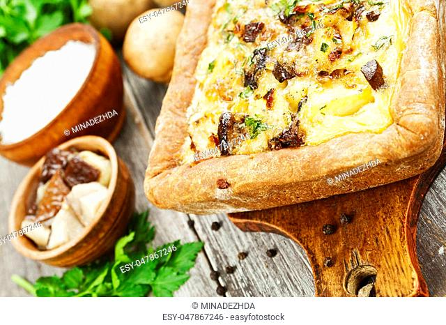 Pie with mushrooms and potatoes on the table