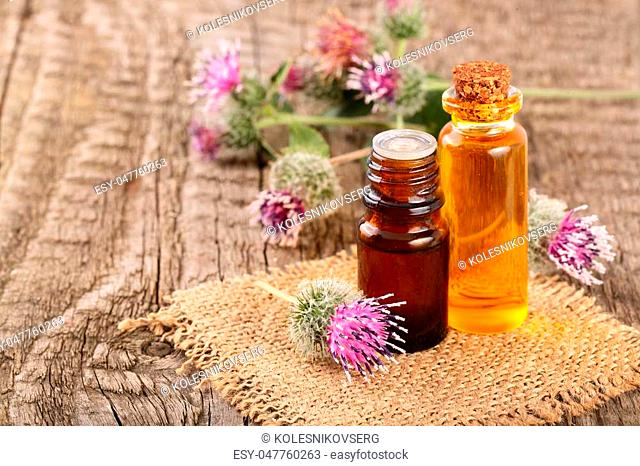 burdock oil in glass bottle and burdock flowers on an old wooden background