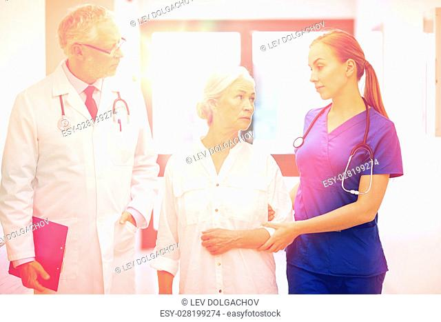 medicine, age, health care and people concept - male doctor with clipboard, young nurse and senior woman patient talking at hospital corridor