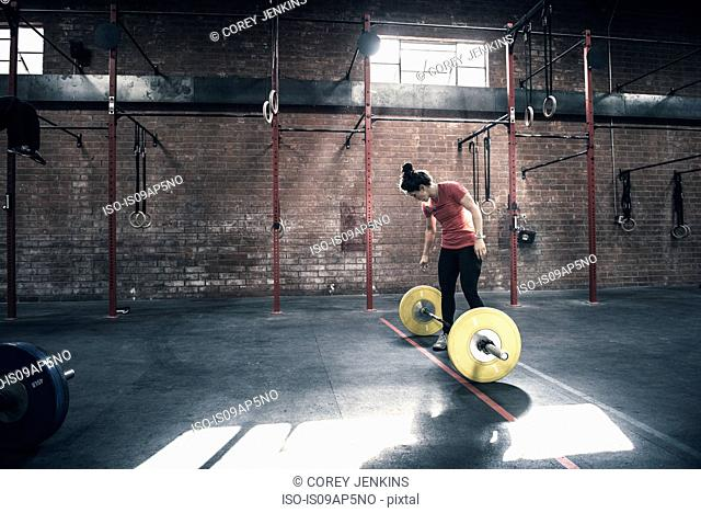Young woman preparing to lift barbell in gym