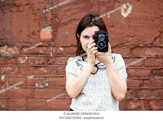 Female photographer with old retro camera on a background old vintage brown brick wall. Selective focus on camera and hands of model. Natural light