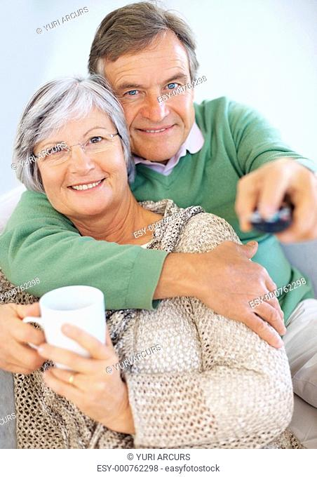 Smiling senior couple sitting together and watching television , man changing the channels