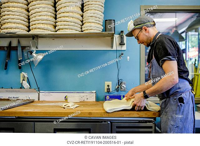 A smiling professional baker folds pastry dough on a floured counter