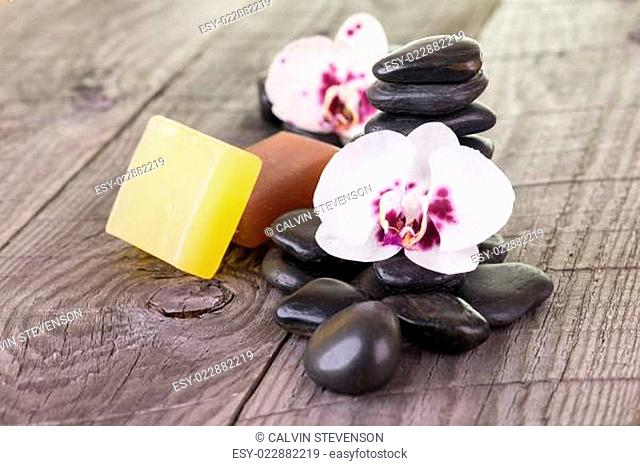 White Moth orchids, soaps and black stones on weathered deck