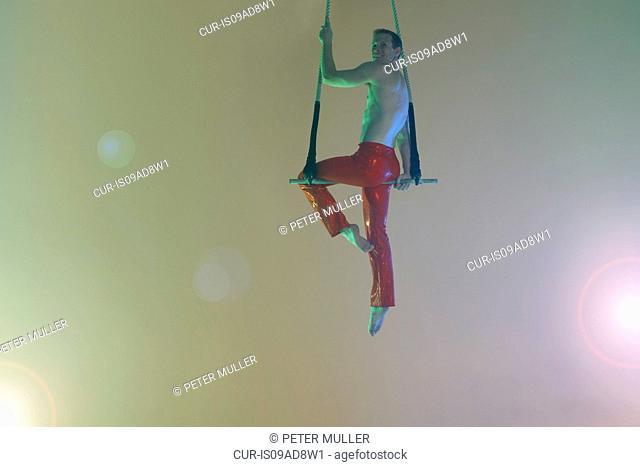 Trapeze artist sitting on trapeze