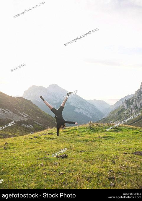 Spain, Cantabria, Young woman performing handstand in Picos de Europa