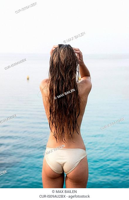 Rear view of young woman wearing bikini bottoms with hands in hair at coast