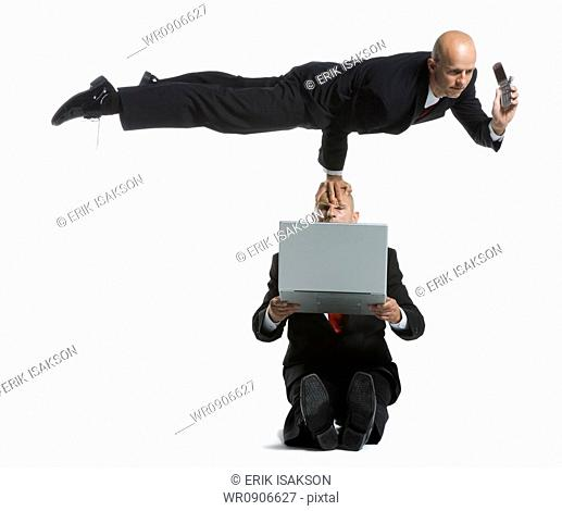 Two male acrobats in business suits performing