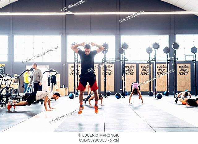 Man training in gym, jumping in mid air