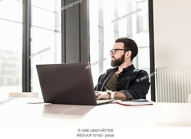 Young casual businessman sitting in office