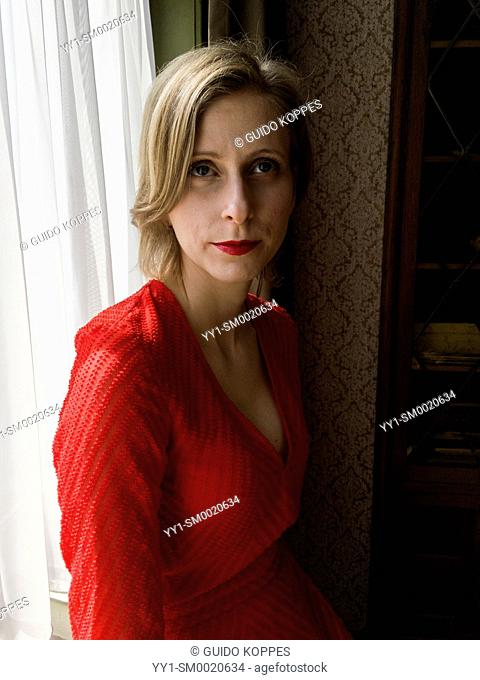 Tilburg, Netherlands. Portrait young adult woman wearing a red dress sitting in a window still at home