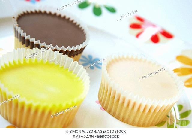 Three cup iced cup cakes on a decorative paper plate