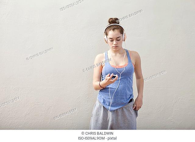 Teenage girl listening to smartphone music in ballet school
