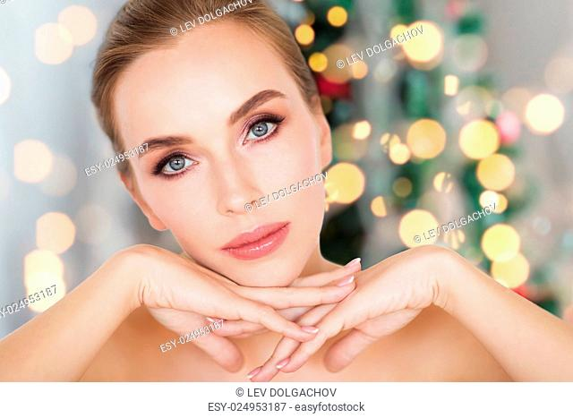 beauty, people, holidays and bodycare concept -beautiful young woman face and hands over christmas tree lights background