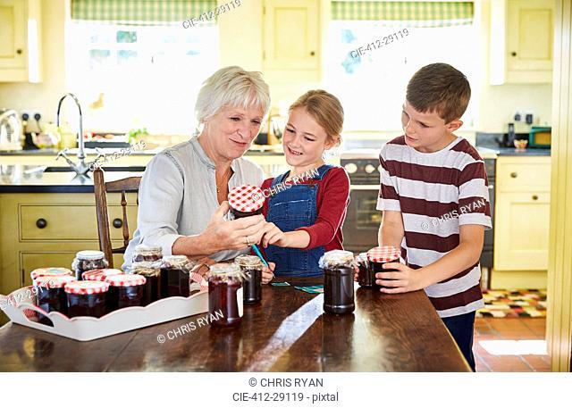 Grandmother canning jam with grandchildren in kitchen