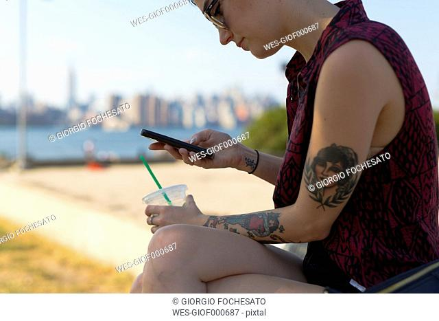 USA, New York City, Brooklyn, tattooed woman sitting on a bench looking at her smartphone