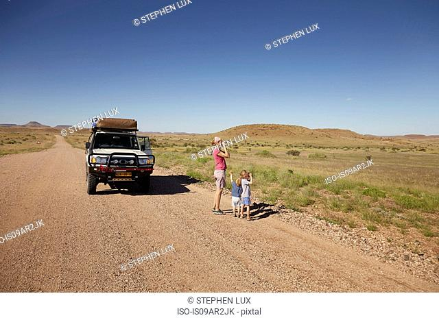 Off road vehicle parked while mother and children look at view, Sesfontein, Kaokoland, Namibia