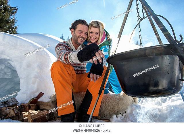 Austria, Salzburg, Couple preparing tea near igloo, smiling