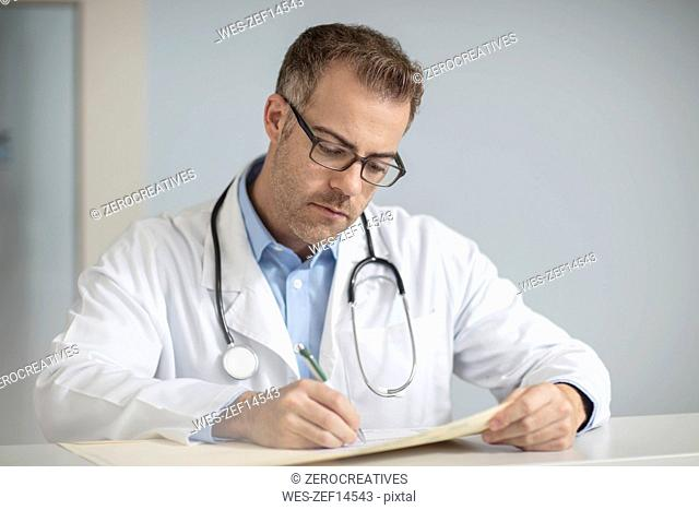 Doctor doing paperwork at desk