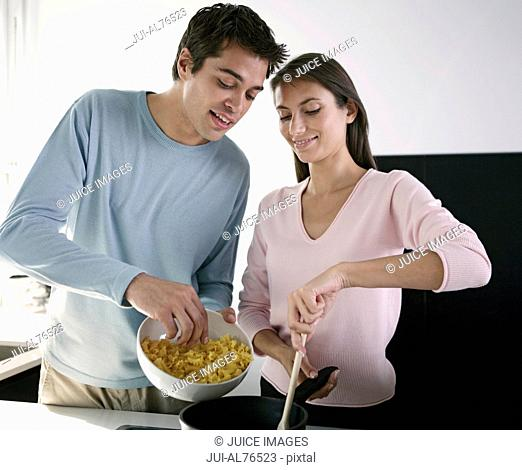 Portrait of a young couple cooking in kitchen