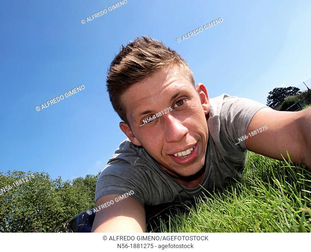 England, London, Portrait of man lying on grass