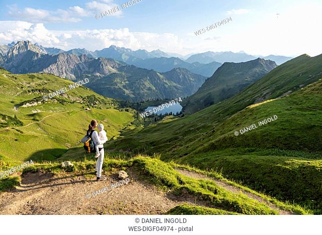Germany, Bavaria, Oberstdorf, mother and little daughter on a hike in the mountains looking at view