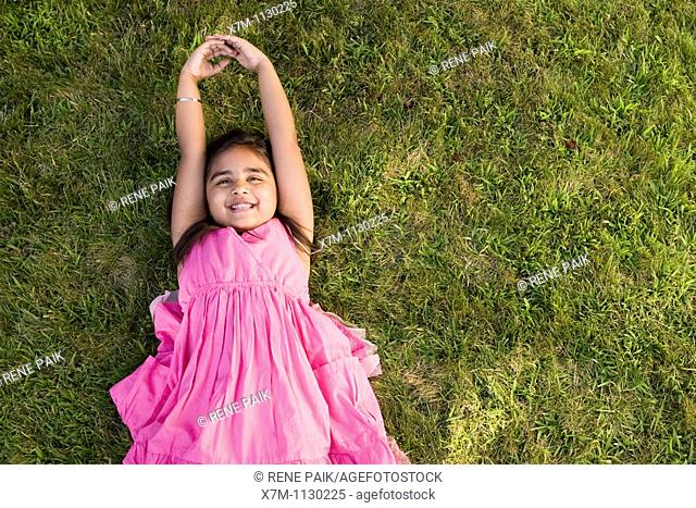 A little Indian girl relaxing on the grass