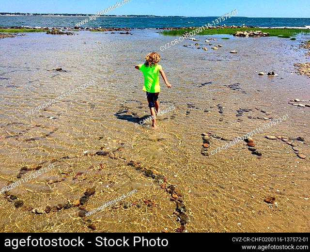 boy running though tide pool with rock art at beach in summer