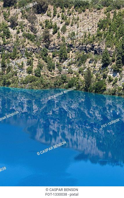 Reflection of trees and rock in blue water