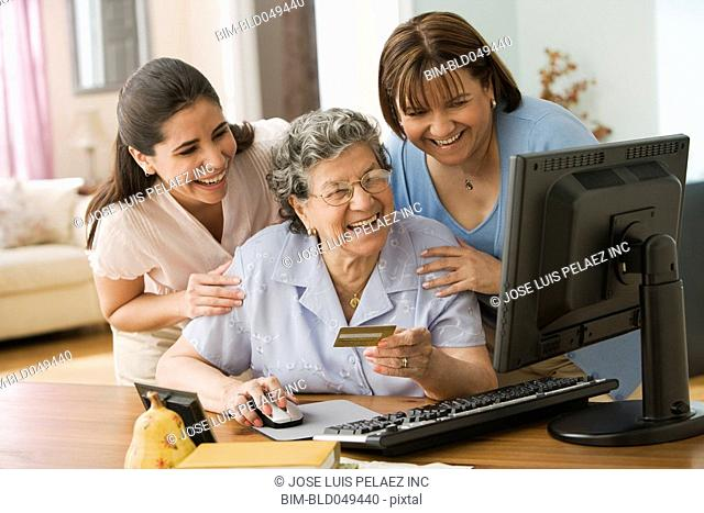 Hispanic mother and daughters shopping online