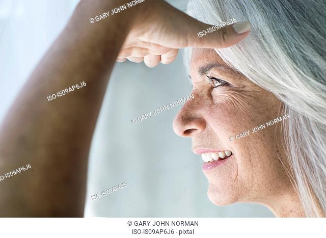 Close up of mature woman with hand shielding eyes