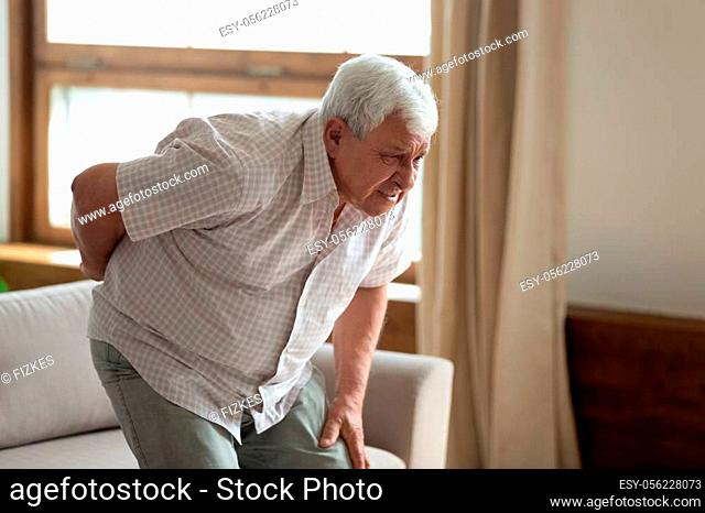 Senior grey haired 70s years man got up from couch writhes in pain felt sharp ache suffers from low back strain, touch loin reduce backache