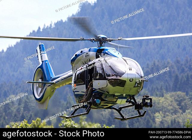 13 July 2020, Baden-Wuerttemberg, Oppenau: A police helicopter lands near the community of Oppenau on a sports field, which serves as a meeting point for the...