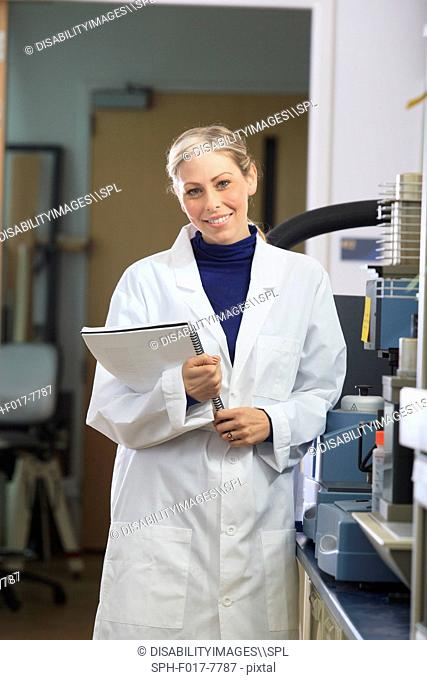 Engineering student holding user manual for chemical analysis instrument in chemical analysis laboratory