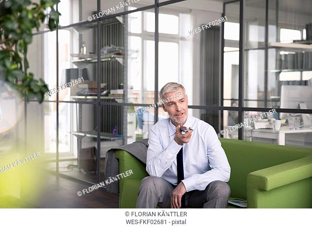 Mature businessman sitting on a couch in the office, using smartphone